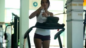 Young woman doing exercises on treadmill in gym. At the end of running drinking water and leaves. 1920*1080 stock footage