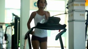 Young woman doing exercises on treadmill in gym. At the end of running drinking water and leaves. Fitness 1920x1080 stock footage