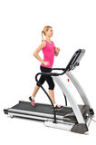 Young woman doing exercises on treadmill. Isolated, motion blur on moving parts Royalty Free Stock Photos
