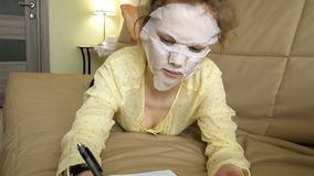 Young woman doing facial mask mask with cleansing mask, clicks on couch with smartphone at home. 4k stock images