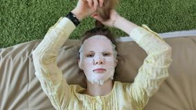 Young woman doing facial mask mask with cleansing mask, clicks on couch with smartphone at home. 4k stock image