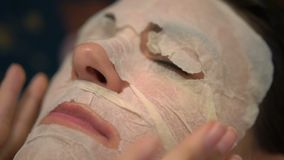 Young woman doing a facial mask close up. stock footage