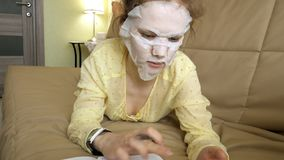 Young woman doing facial mask mask with cleansing mask, clicks on couch with smartphone at home. 4k stock photo