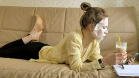 Young woman doing facial mask mask with cleansing mask, clicks on couch with smartphone at home. 4k royalty free stock photos