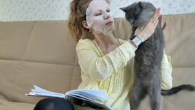 Young woman doing facial mask mask with cleansing mask on face in kitchen at home cat. 4k Stock Images