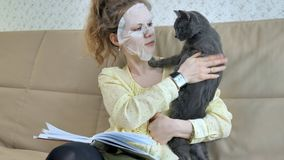 Young woman doing facial mask mask with cleansing mask on face in kitchen at home cat. 4k Royalty Free Stock Photos