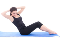Young woman doing fitness exercise on blue fitness mat isolated Stock Images
