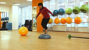 Young woman doing fitness exercise with bosu ball. Rostov on Don, Russian Federation – January 05, 2014: Young woman doing fitness exercise with bosu ball stock video footage