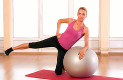 Young woman doing fitness exercise with fit ball. Stock Photos