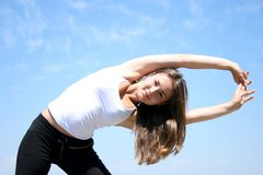 Young woman doing fitness exercises. Against blue sky Royalty Free Stock Photos