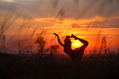 Young woman doing flexible dance move during sunset. royalty free stock image