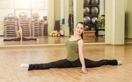 Young woman doing front split in fitness class Stock Photos