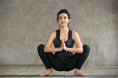 Young woman doing Garland exercise. Young sporty woman practicing yoga, doing Garland exercise, Malasana pose, working out, wearing sportswear, black pants and Royalty Free Stock Images