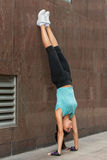 Young woman doing handstand exercise against the wall on the city street. Stock Photo