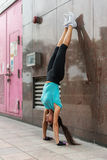 Young woman doing handstand exercise against the wall on the city street. Young woman doing handstand exercise against the wall on the city street Stock Photos
