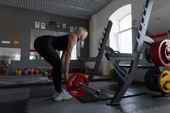 Young woman doing heavy exercise at the gym with a barbell. Girl in great shape doing squats in a fitness studio. Side view. Young woman doing heavy exercise at royalty free stock photography