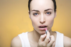 Young woman doing her makeup with a lipstick Stock Photography