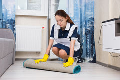 Young woman doing the housekeeping. Young woman dressed in a neat uniform and white apron doing the housekeeping bending down to roll a mat in a living room to Royalty Free Stock Images