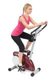 Young woman doing indoor biking exercise. On white background Stock Photography