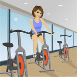 Young woman doing indoor biking exercise at gym Royalty Free Stock Images