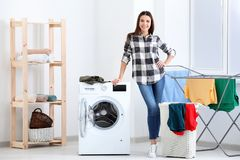 Young woman doing laundry. At home stock images