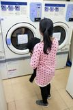 Woman doing laundry. Young woman doing laundry in the laundry room royalty free stock photo