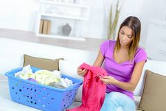 Young woman doing laundry work in living room at home. Female stock photo