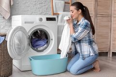 Young woman doing laundry. At home stock photography