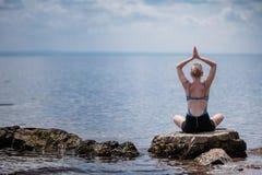 Young Woman doing Lotus Yoga Position Stock Photos