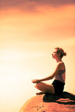 Young Woman doing Lotus Yoga Position in Front of the Ocean. During Sunset stock photos