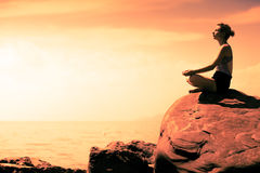 Young Woman doing Lotus Yoga Position in Front of the Ocean. During Sunset stock images