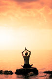 Young Woman doing Lotus Yoga Position in Front of the Ocean. During Sunset stock photo