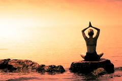 Young Woman doing Lotus Yoga Position in Front of the Ocean Stock Photography