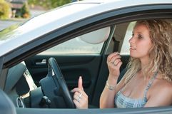 Young woman doing make up in car Royalty Free Stock Photo