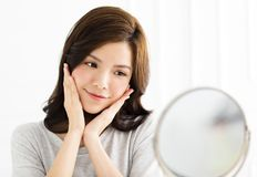 Woman doing makeup in front of mirror Stock Image