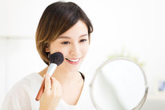 Young woman doing  makeup in front of the mirror Royalty Free Stock Photos