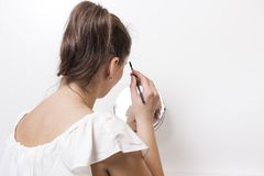 Young woman doing makeup. The girl paints eyelashes. royalty free stock photo