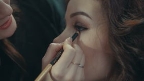 Young woman doing makeup on a model. stock footage