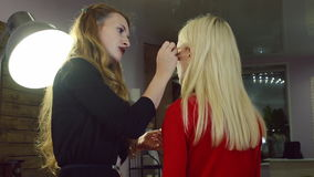 Young woman doing makeup on a model in a beauty salon. stock video footage