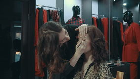 Young woman doing makeup on a model in the boutique of women`s clothing. A young girl stylist applies to the eyelids of the brunette model a dark eye shadow stock video