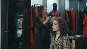 Young woman doing makeup on a model in the boutique of women`s clothing. A young girl stylist applies to the lower eyelids of the brunette model a dark eye stock video footage