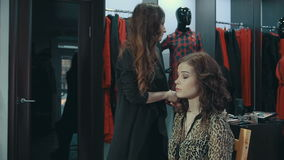 Young woman doing makeup on a model in the boutique of women`s clothing. Young woman doing makeup on a model in the boutique with a large cabinet full of stock footage