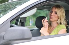 Young woman doing maleup in car Royalty Free Stock Image