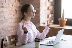 Young woman doing meditation in office at work royalty free stock images
