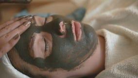Young woman doing a mud face mask. Young woman doing a mud facial mask at spa salon Natural Regenerating Mask. Close-up stock footage