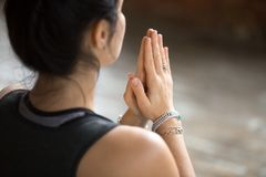 Young woman doing namaste gesture, closeup. Namaste gesture close up photo, young attractive woman practicing yoga, working out, wearing wrist bracelets and stock image