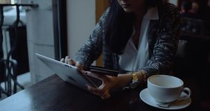Young woman doing online shopping on tablet computer in cafe. Details hands. stock video footage
