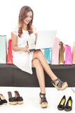 Young woman doing online transaction and sitting between shoppin Stock Photos