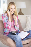 Young Woman Doing Paperwork And Using Mobile Phone At Home Stock Photos