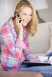 Young Woman Doing Paperwork And Using Mobile Phone At Home Royalty Free Stock Image